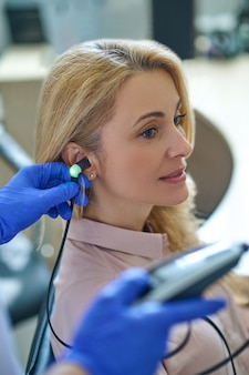 Lovely pensive caucasian female patient sitting still during an audiometry test performed by a medical professional