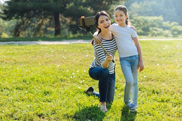 素敵な写真。魅力的な楽しい若い母親と娘がお互いに抱き合って、公園で自撮り棒を使って自分撮りをします