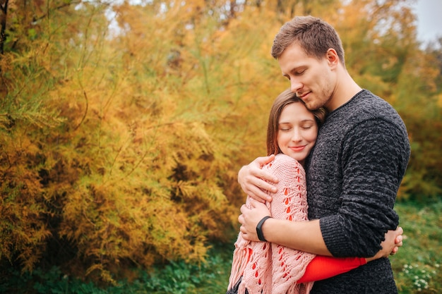 Lovely picture of couple embracing. they keep eyes closed and enjoying the moment. people stand in autumn park.
