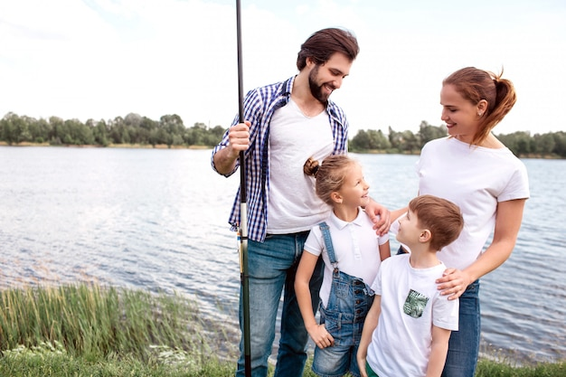 Lovely picture of happy family standing together outside. guy is holding fish-rod and looking at daughter while she is looking at her mom. woman is looking at daughter when boy is looking at father.
