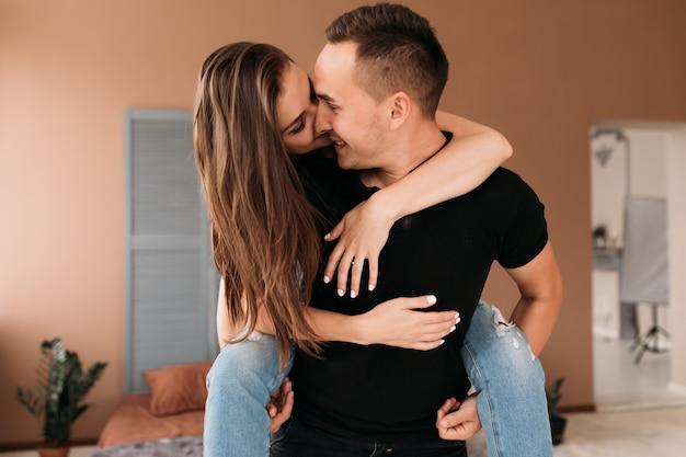 彼のガールフレンドを背中に持つ若い男の素敵な写真