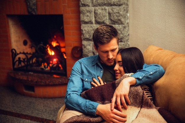 Lovely picture of young couple sleeping together. she leans to him on his chest. model covers with blanket. guy embrace her. they sit near fireplace.