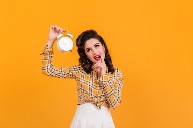 大きな時計を持っている素敵なピンナップガール。黄色の背景で隔離の身なりのよいヨーロッパの女性のスタジオショット。