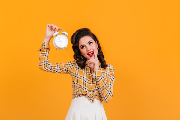 Lovely pinup girl holding big clock. studio shot of well-dressed european woman isolated on yellow background.