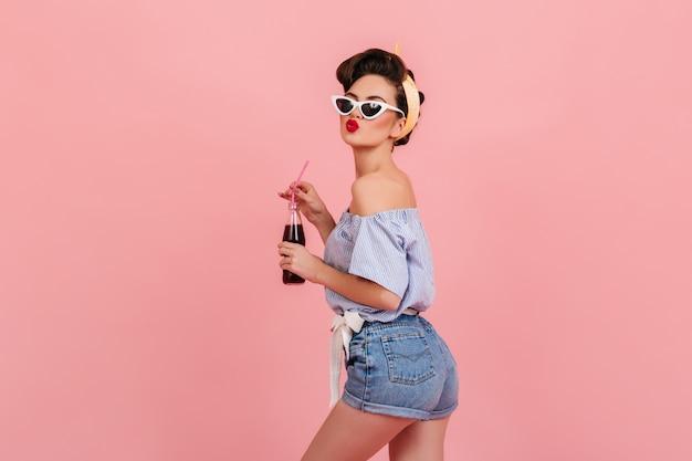 ポジティブな感情を表現するデニムショートパンツの素敵なピンナップガール。ピンクの背景に飲み物とボトルを保持しているサングラスの嬉しいブルネットの女性のスタジオショット。