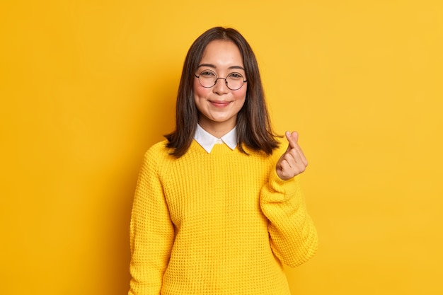 Милая довольная азиатская женщина делает корейский жест улыбки, нежно выражая кому-то любовь