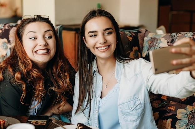사랑스러운 더하기 크기의 여자와 그녀의 매력적인 여자 친구는 커피를 마시고 케익을 먹고 커피 숍에 앉아 셀카를하면서 재미있는 얼굴을하고 있습니다.