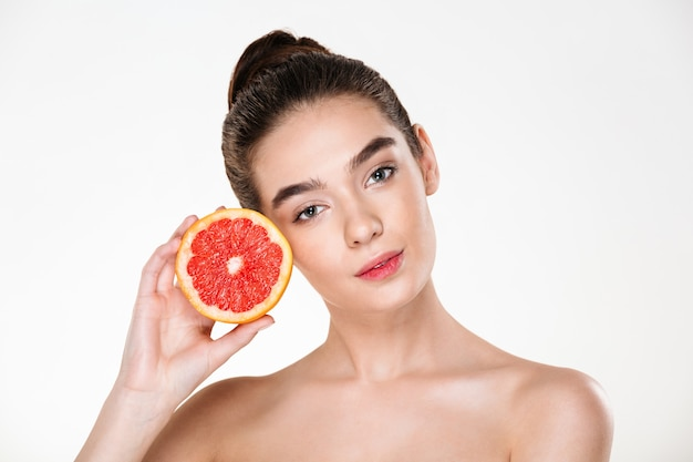 Lovely portrait of pretty half-naked woman with natural makeup holding juicy grapefruit near her face and looking