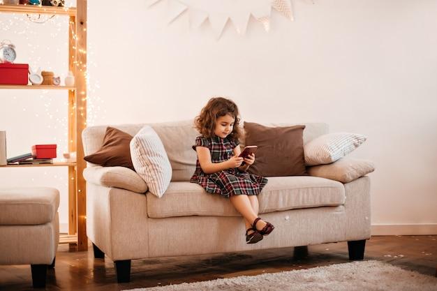 Прекрасная девочка десятилетнего возраста в платье, сидящем на софе. крытый снимок фигурного маленького ребенка, позирующего в гостиной.