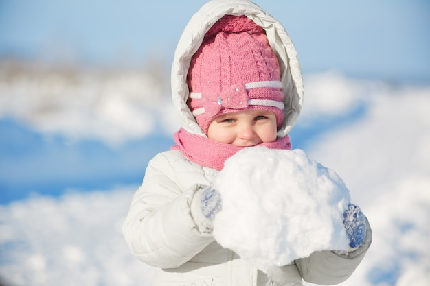Lovely pretty little girl dressed in warm winter clothes, holds snowball relaxes outdoor during frosty winter weather, going to make snowman