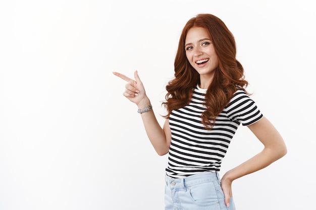 巻き毛の髪型、半回転の軽薄でコケティッシュなポーズの素敵なかわいい赤毛の女の子、友好的で面白がって笑っているカメラを回し、指を左方向に向け、コピースペース、白い壁を提案する