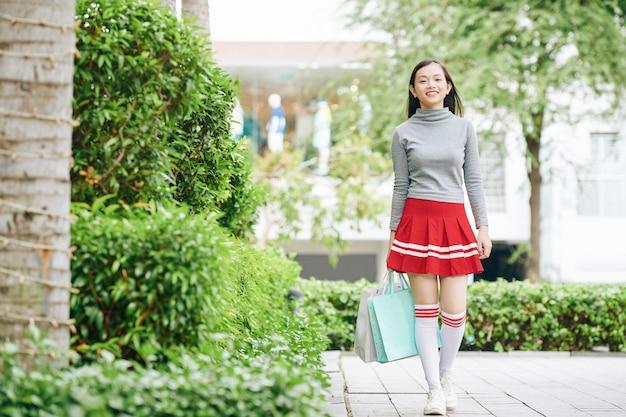 買い物袋を手に歩いている素敵なかわいいベトナムの10代の少女
