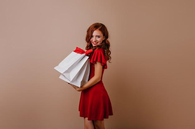 쇼핑 후 포즈를 취하는 사랑스러운 red-haired 소녀. 매력적인 여성 쇼핑 중독.
