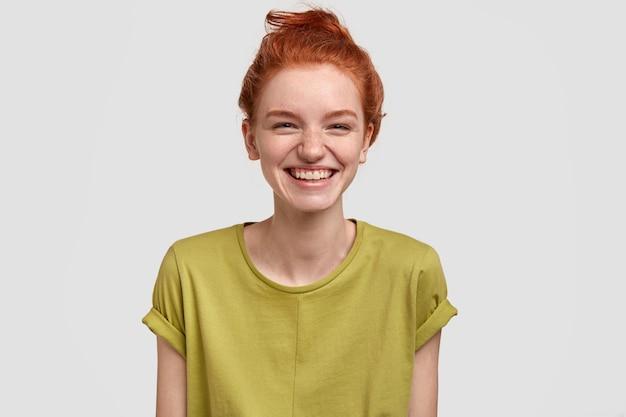 Bella ragazza dai capelli rossi con espressione positiva, ride mentre guarda un divertente programma televisivo, si gode il fine settimana, vestita con una maglietta verde, ha la pelle lentigginosa, isolata sopra il muro bianco, divertita dall'idea comica