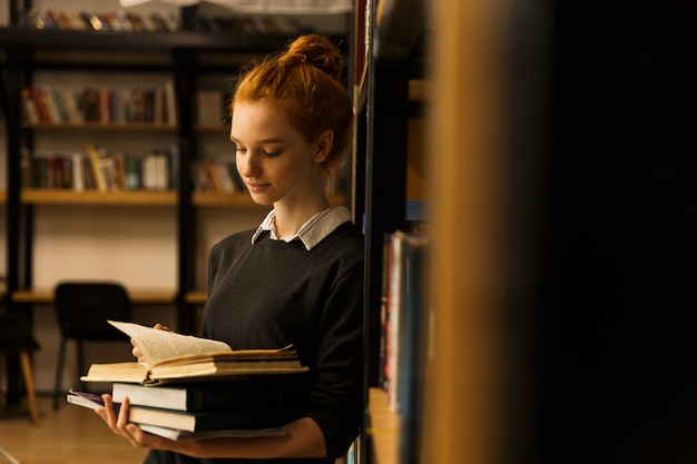 Lovely red haired teenage girl carrying books at the library