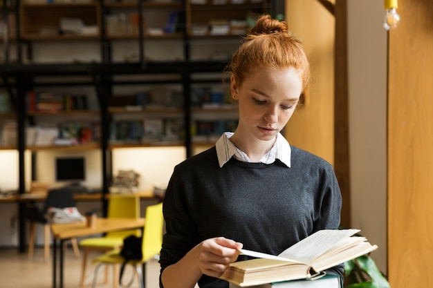 Lovely red haired teenage girl carrying books