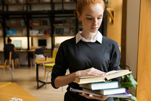 Lovely red haired teenage girl in earphones carrying books