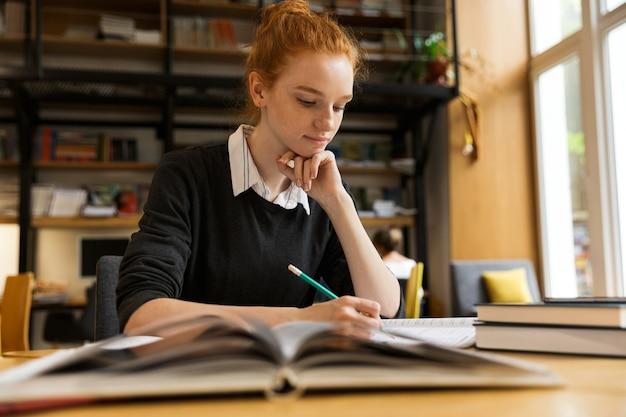Милая рыжая девочка-подросток учится за столом