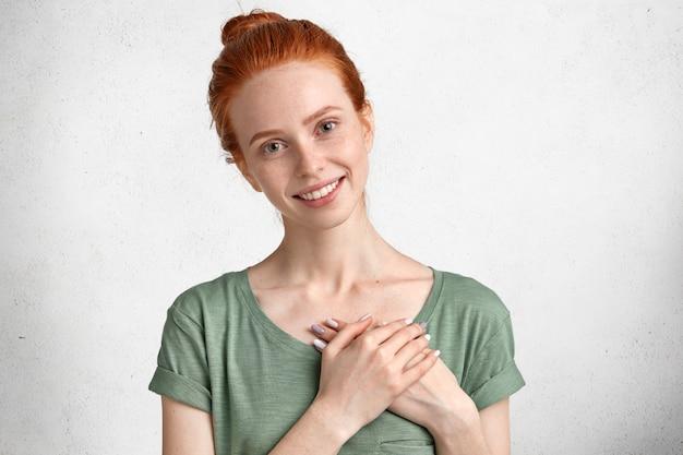 Милая рыжеволосая девушка с позитивным выражением лица, держит руки на груди, выражает свою преданность и дружелюбие