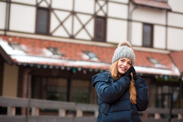 キエフの路上でポーズをとってトレンディな衣装を着て素敵な赤い髪の若い女性