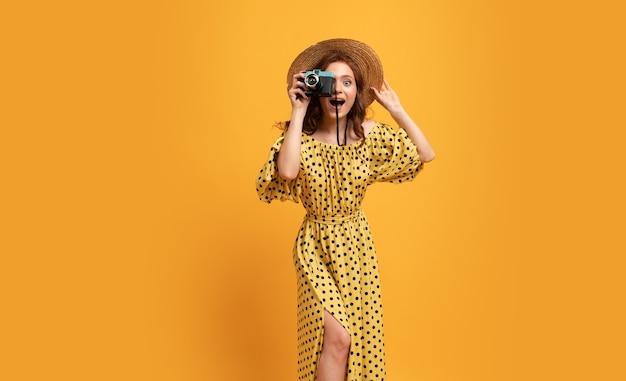 Прекрасная рыжая женщина в соломенной шляпе и стильном летнем платье позирует на желтом