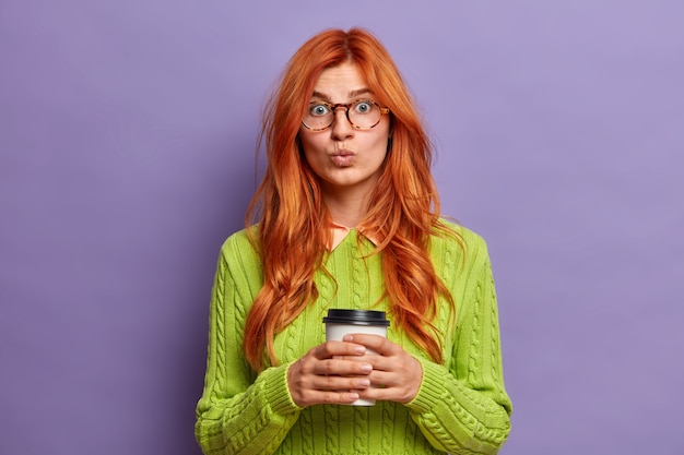 사랑스러운 redhaired 젊은 여자는 입술을 둥글게 유지하고 놀랍게도 일회용 커피 컵을 보유하고 있으며 여가 시간에 녹색 점퍼를 착용합니다.