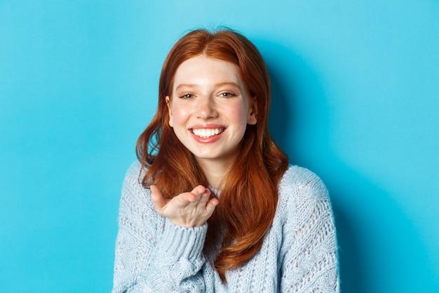 사랑스러운 빨간 머리 여성 모델이 웃고, 파란색 배경에 서서 카메라에 공기 키스를 보냅니다.
