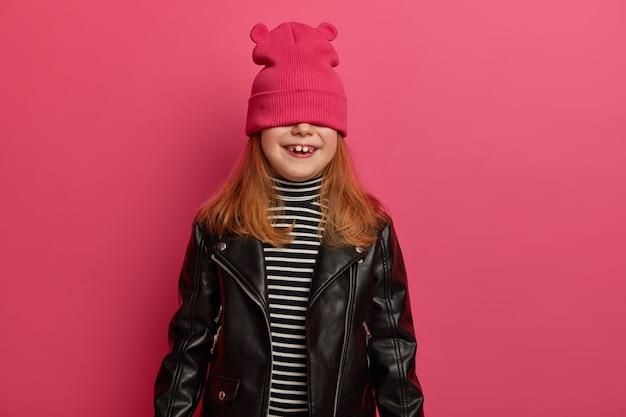 素敵な赤毛の女の子はかくれんぼゲームをし、前向きな感情で驚きを待ち、ピンクの帽子で目を覆い、縞模様のジャンパーと革のジャケットを着て、楽しんで、屋内でポーズをとる