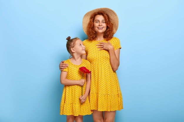 Lovely redhead mother and daughter posing in similar dresses