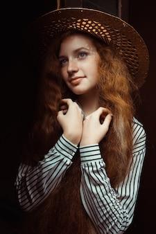 古い木製のドアの近くでポーズをとる麦わら帽子の長い巻き毛の素敵な赤毛の女性