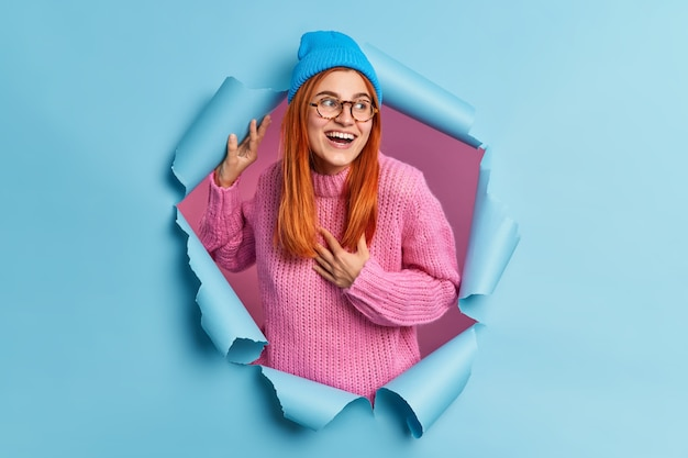 Lovely redhead young woman keeps hand on chest and looks positively aside notices funny thing wears hat pink knitted sweater breaks through paper hole