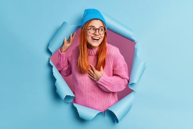素敵な赤毛の若い女性が胸に手を置いて、前向きに脇を向いていることに気づきます面白いものが帽子をかぶっていますピンクのニットセーターが紙の穴を突破します