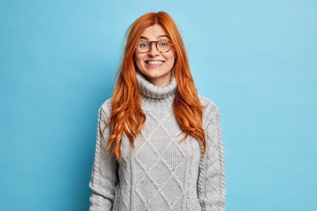 유쾌하게 따뜻한 스웨터를 입고 유럽의 모습으로 미소 짓는 사랑스러운 빨간 머리 젊은 여성이 좋은 소식을 듣고 긍정적 인 감정을 표현한다.