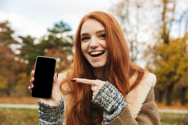 ベンチに座って、携帯電話を使用して、空白の画面の携帯電話を表示しながら音楽を聴いている素敵な赤毛の少女