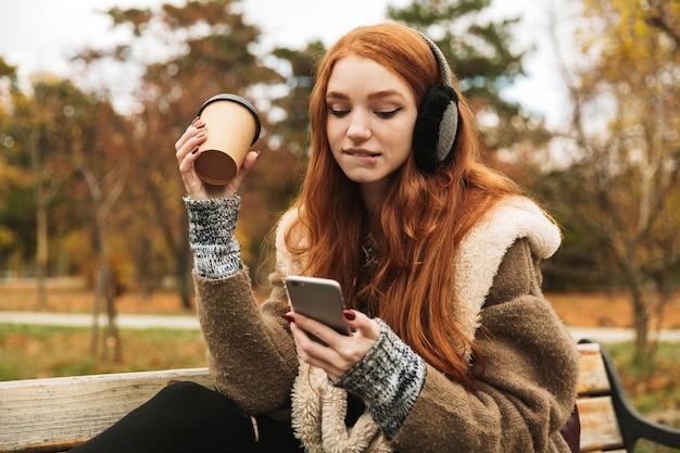 Милая рыжеволосая девушка слушает музыку в наушниках, сидя на скамейке и используя мобильный телефон