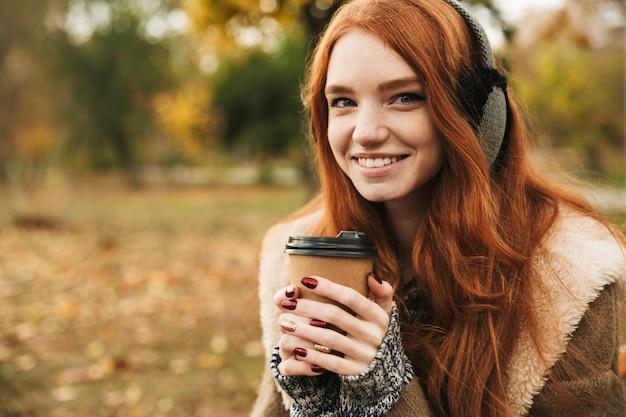 Милая рыжеволосая девушка слушает музыку в наушниках, сидя на скамейке и пьет кофе