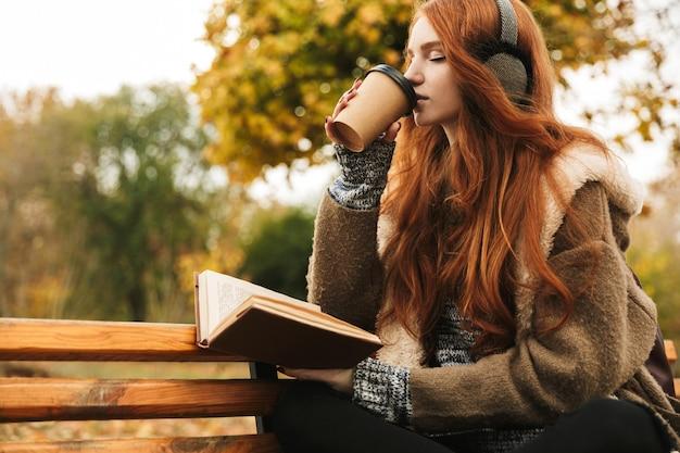 Милая рыжеволосая девушка слушает музыку в наушниках, сидя на скамейке, читает книгу, пьет кофе