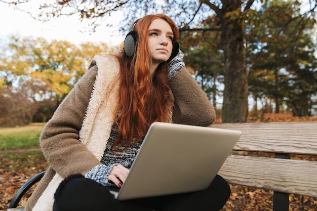 Милая рыжеволосая девушка слушает музыку в наушниках, сидя на скамейке, используя портативный компьютер