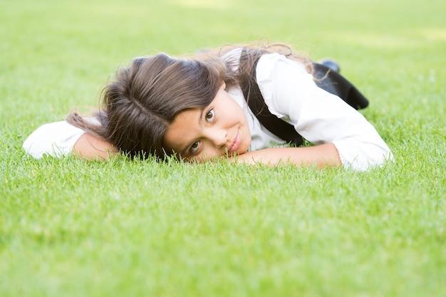 Прекрасный расслабленный вид. очаровательная девушка со школьным взглядом расслабляется на зеленой траве. симпатичный маленький ребенок имеет школьный вид в формальной одежде. модный образ маленькой фотомодели.
