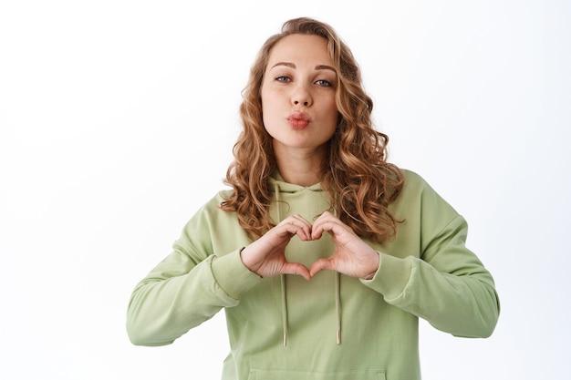 素敵なロマンチックな女の子は私があなたを愛していると言い、白い壁の上に立って、ハートのサインとキスの顔を示しています
