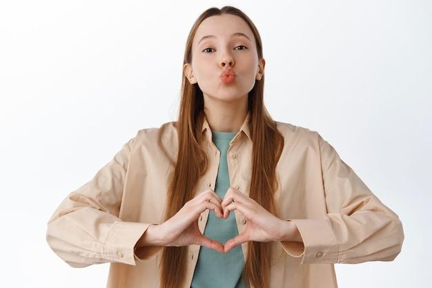 Bella ragazza romantica mostra il segno del cuore e bacia la faccia, le labbra pucker aspettano il bacio, dicono ti amo, in piedi in abiti casual contro il muro bianco