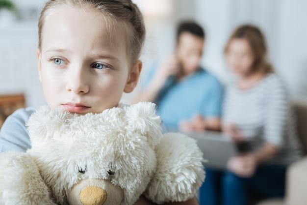 사랑스러운 슬픈 파란 눈 어린 소녀가 그녀의 테디 베어를 껴안고 그녀의 부모가 노트북에서 작업하는 동안 혼자 느낌