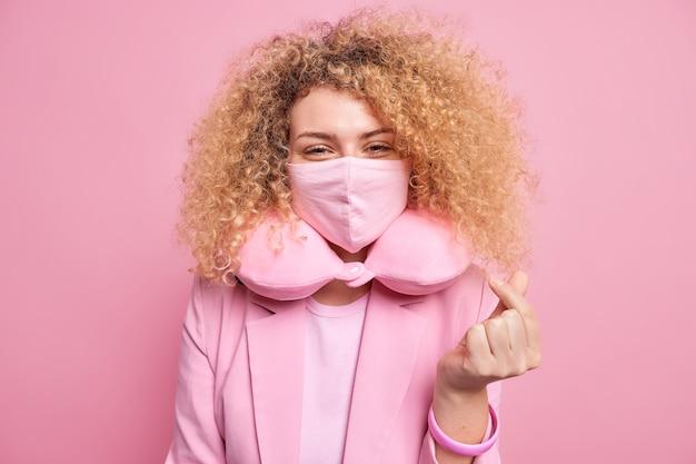 사랑스럽고 만족스러운 곱슬 머리 여자는 사랑을 표현하는 한국인이 코로나 바이러스 공식 복장에 대한 보호 마스크를 착용하고 분홍색 벽 위에 고립 된 편안한 목 베개를 만듭니다. 신체 언어
