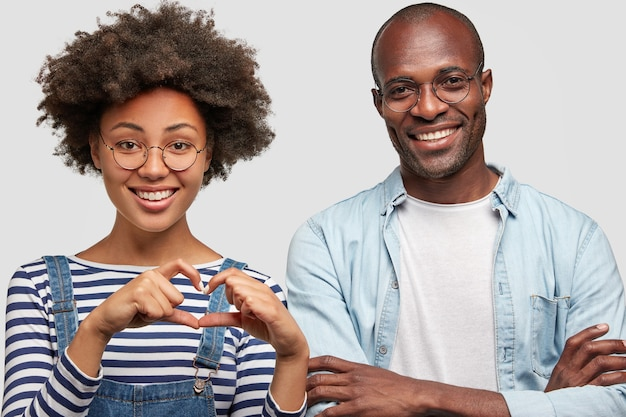 Lovely satisfied curly young african american female makes heart gesture, expresses love and good attitude, stands next to her cheerful dark skinned boyfriend, being in good mood during date