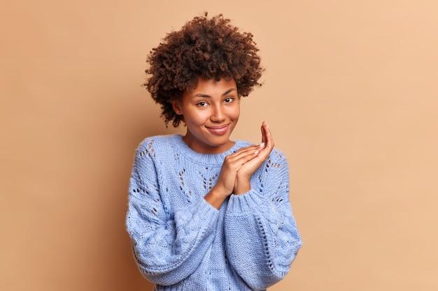 Bella donna soddisfatta con i capelli afro ha un'espressione soddisfatta strofina i palmi e sorride delicatamente con gioia indossa un maglione blu casual vede qualcosa di molto buono composto da un bel piano isolato sopra il muro marrone