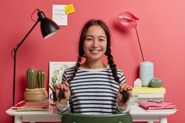 Adorabile studentessa si diverte mentre si prepara per gli esami, ha due lunghe trecce, sorride allegramente, vestita con un maglione a righe, programma il programma per il prossimo mese