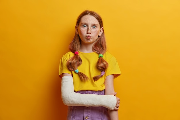 Lovely schoolgirl makes funny expression, pouts lips, has two pony tails, red hair, freckled face, dressed casually, got injured after falling from height, wears cast on broken arm, isolated on yellow