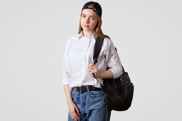 Lovely schoolgirl wears jeand and white shirt, carries rucksack, stands on white, goingt to school. education and learning