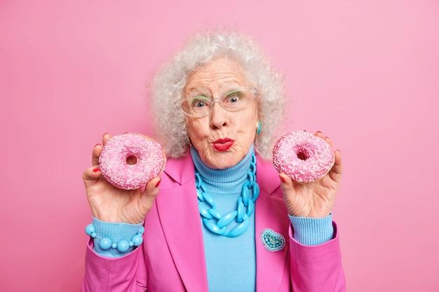 Una bella donna anziana tiene in mano due ciambelle smaltate e mantiene le labbra piegate piacevolmente, vestita con abiti alla moda con collana e braccialetto