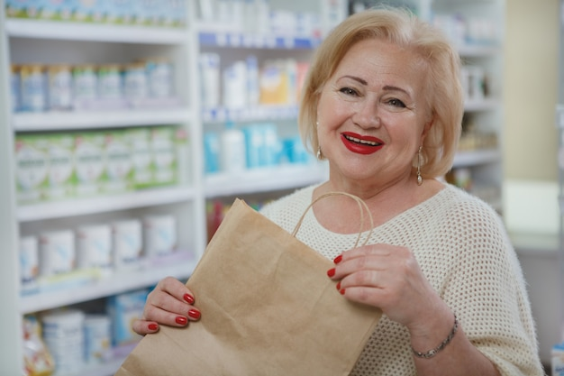 Lovely senior woman shopping at drugstore